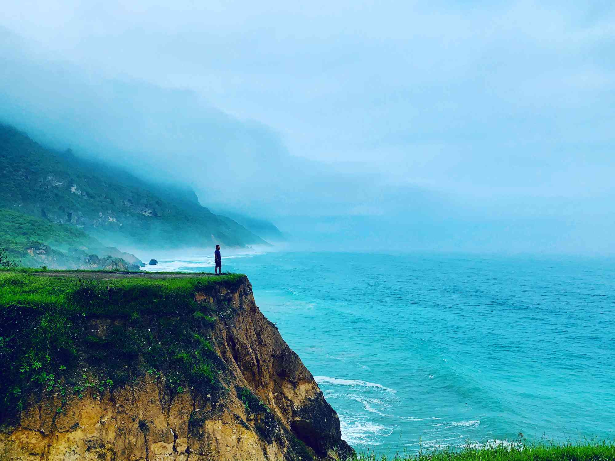 Man standing on a cliff overlooking the sea on a misty day in Salalah, Oman