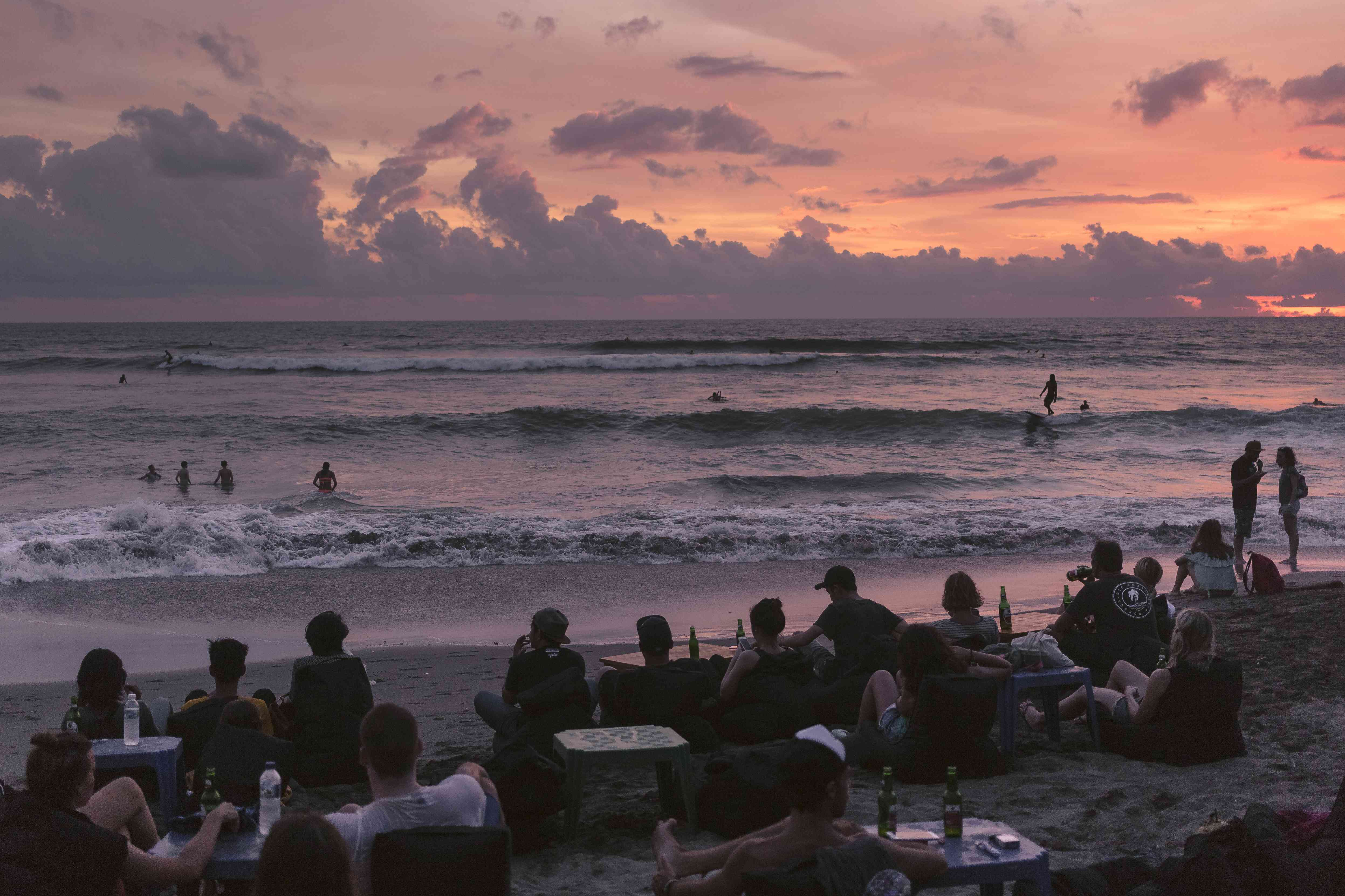 People enjoy drinks and watch sunset on the beach at Canggu, Bali