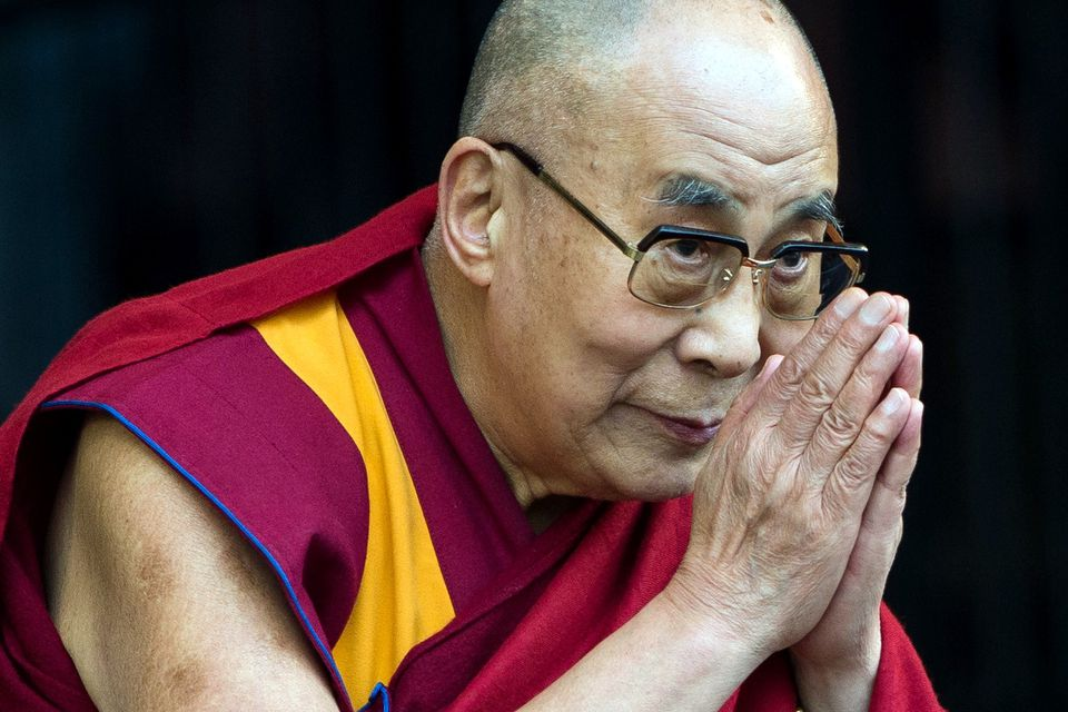 The 14th Dalai Lama, Tenzin Gyatso, puts his palms together in front of his face