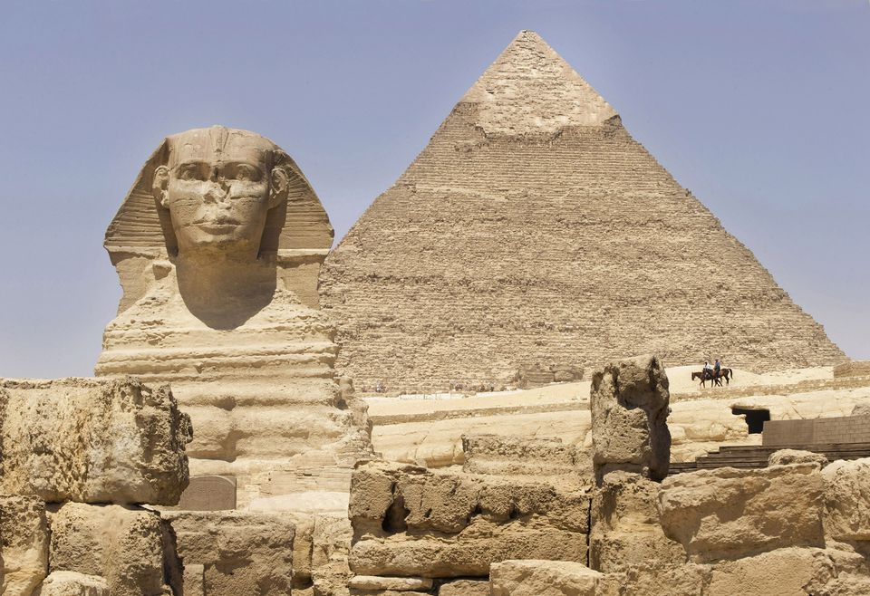 Two people on horseback riding in front of the Great Pyramid of Giza towards a sphinx statue