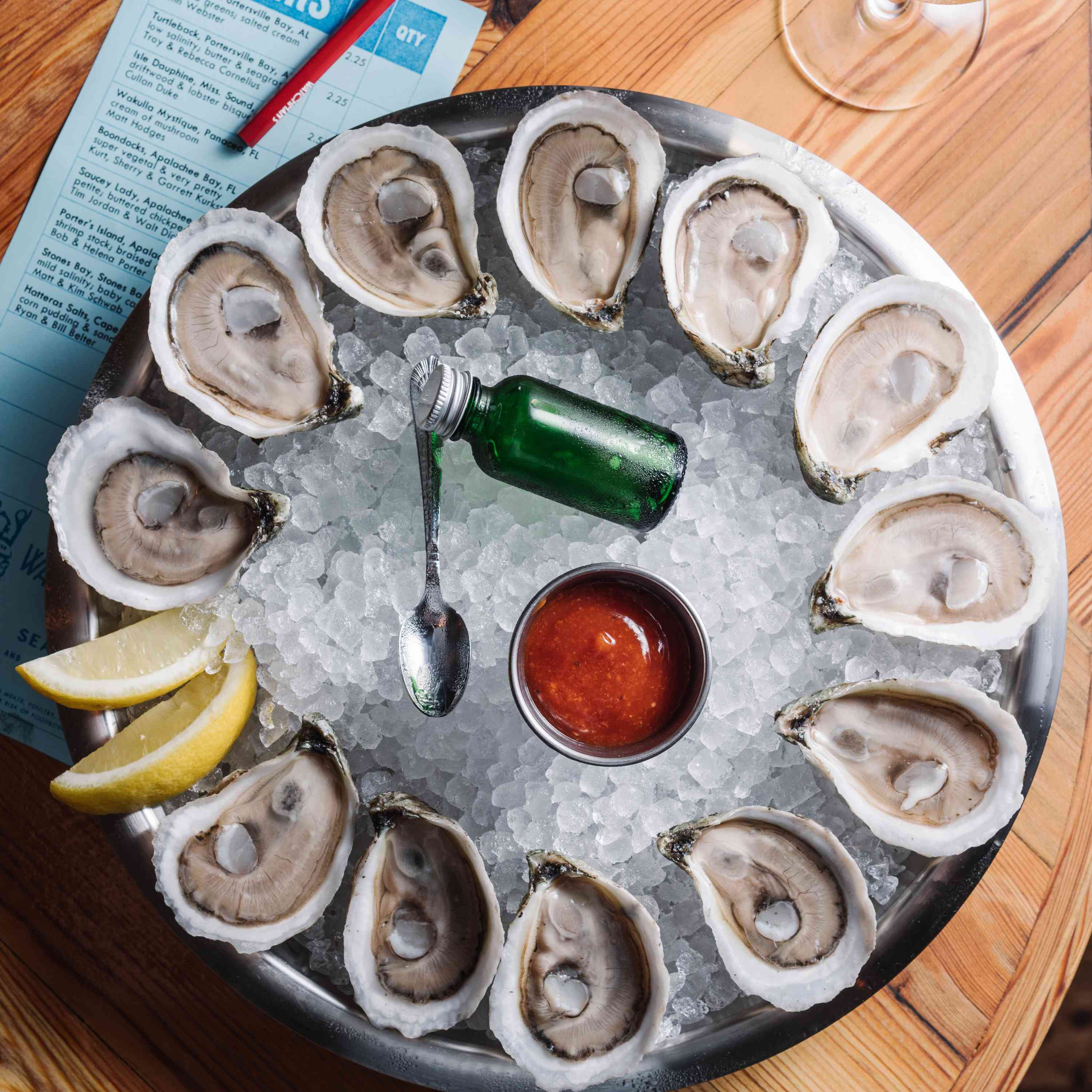 12 raw oysters arranged on the edge of an ice filled bowl with two lemont slices and cocktail sauce, a small spoon and a small, green bottle in the middle