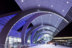 Glowing lights outside the curved modern architectural exterior of Dubai International Airport Terminal 3