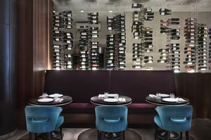 A picture of trendy, low-lit restaurant with a large wine closet behind a set of tables.