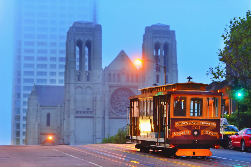 An SF cable car with Grace Cathedral in the background