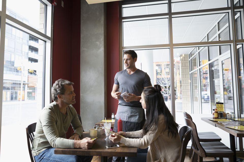 Camarero tomando orden de padre e hija adolescente en la mesa del comedor