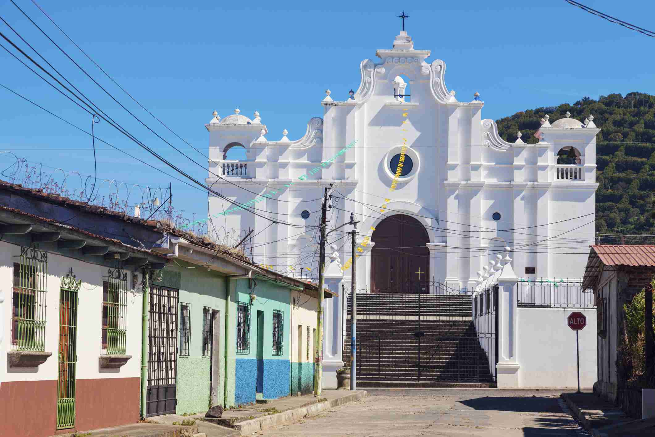 White church in Apaneca, El Salvador with colorful buildings in front of it