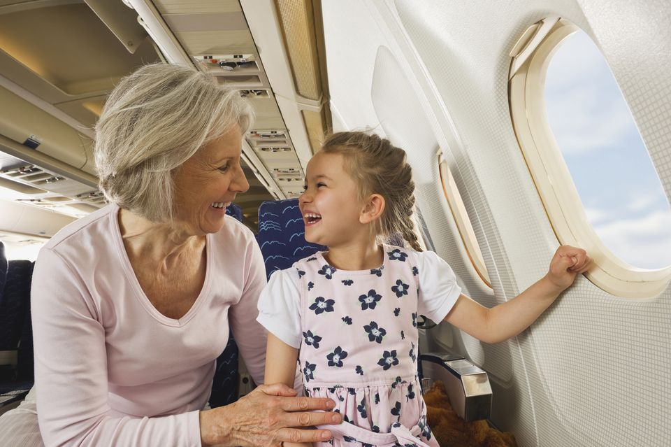 Senior woman and girl smiling beside window in economy class airliner