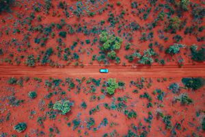 Aerial shot of a blue car driving along a red dirt road