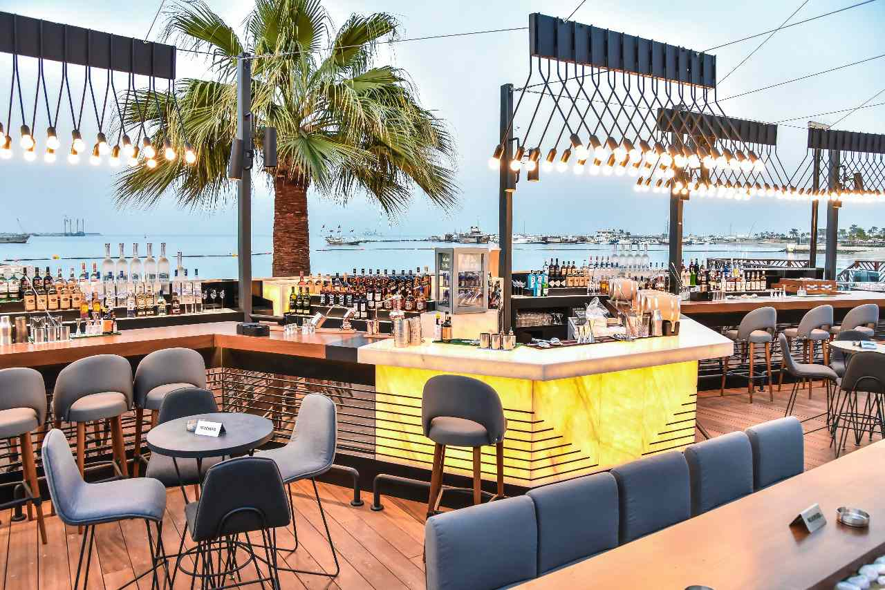 Oudoor lounge with a bar and outdoor lights and a palm tree in the background