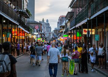 Busy bourbon street with signs lit up at night