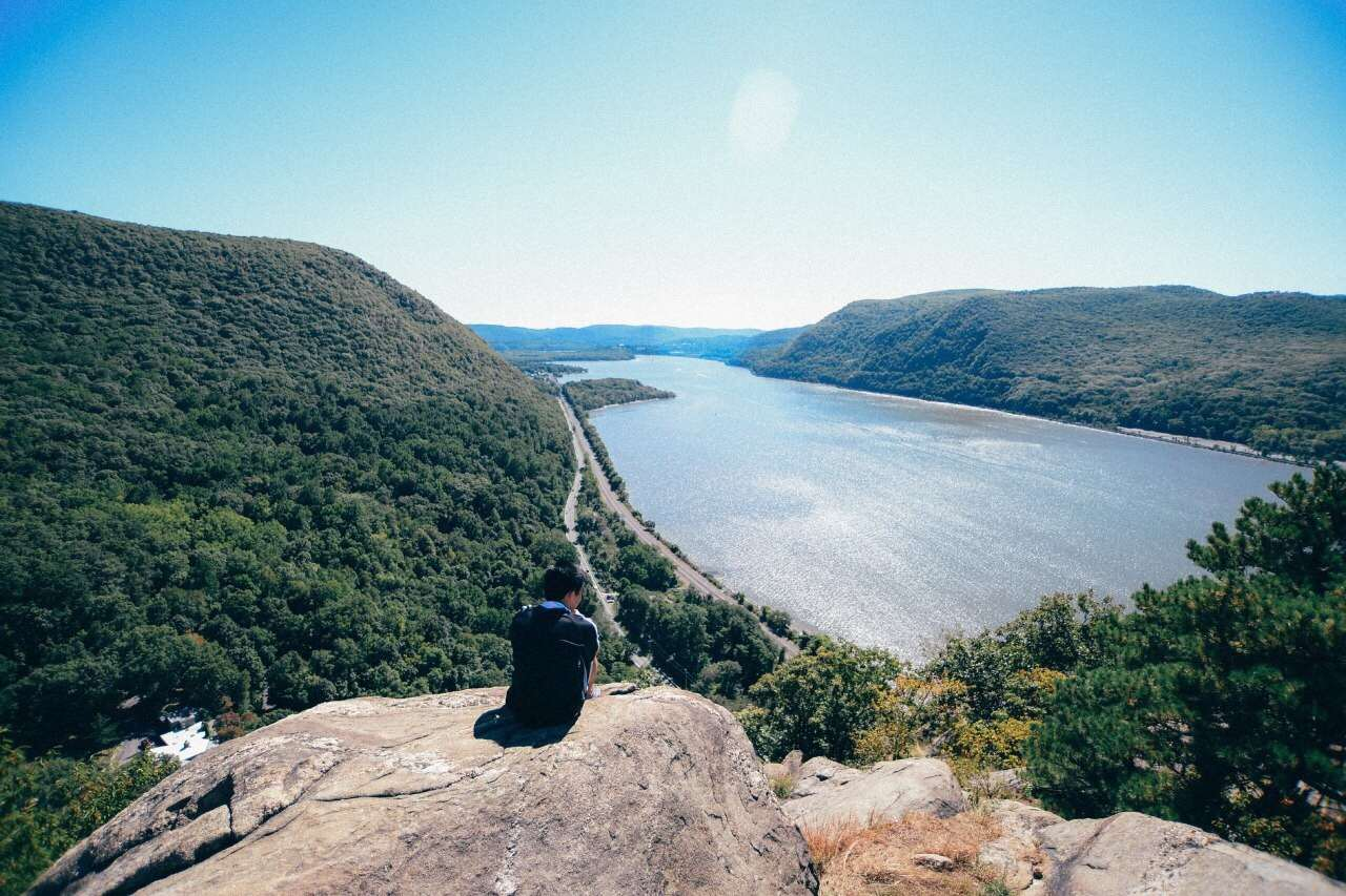 Rear View Of Man Sitting On Breakneck Ridge Against Sky