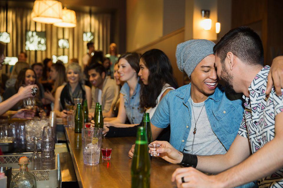 Pareja de homosexuales abrazándose y bebiendo en el bar