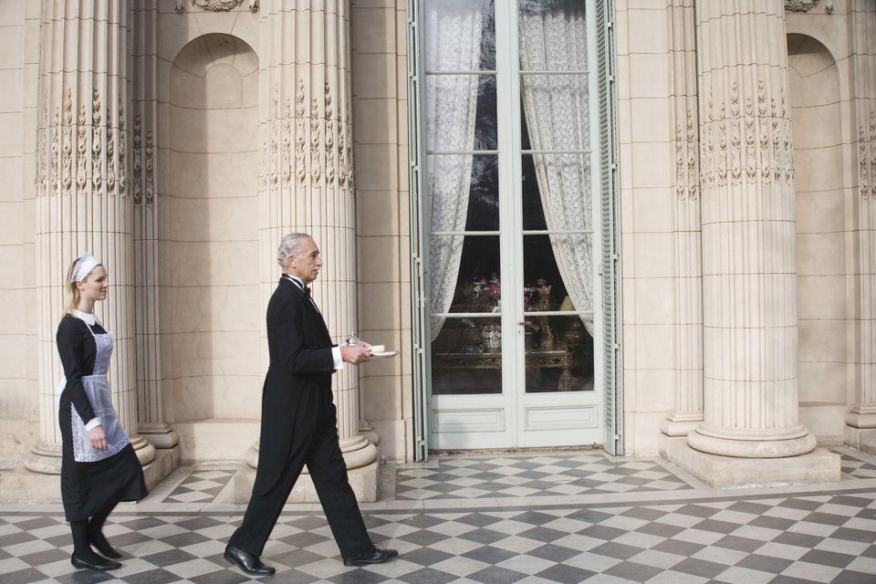 Maid walking behind butler