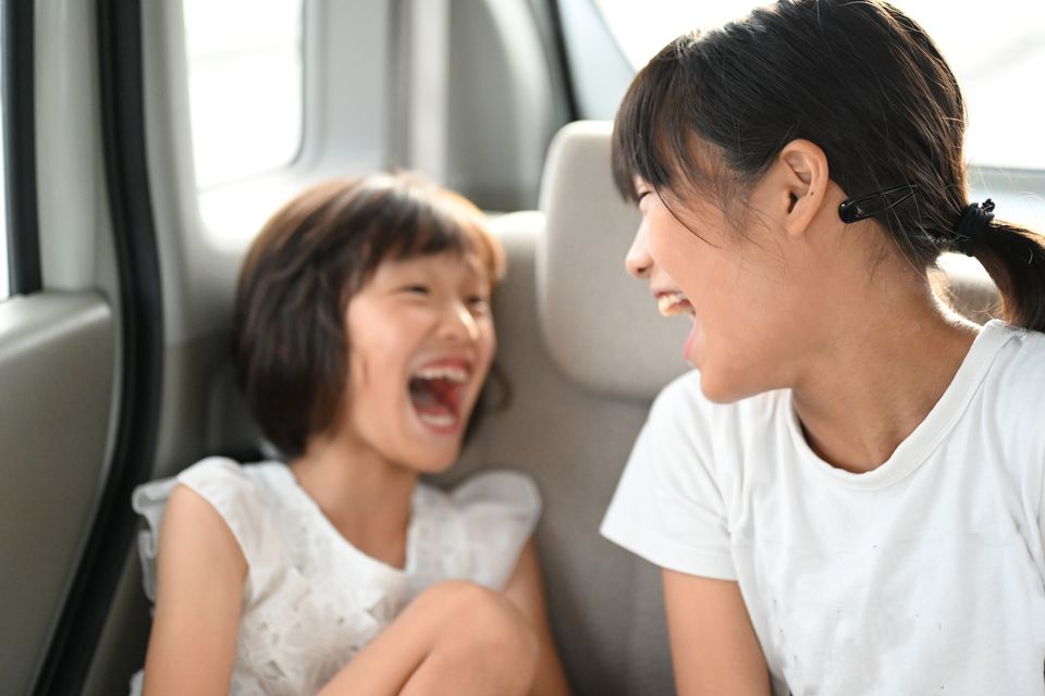 Sisters in the car laughing and playing