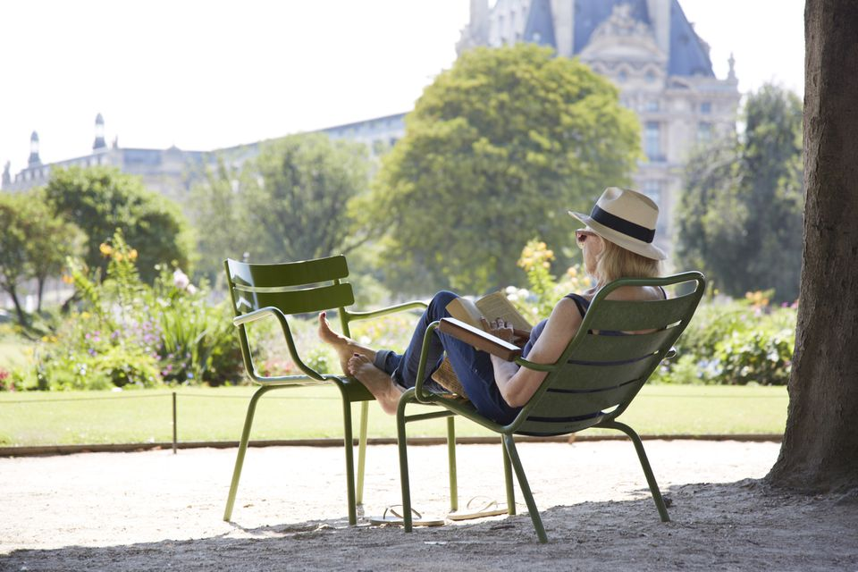 White woman in a hat lounging on two chairs, reading at the Jardin des Tuileries, Paris, France