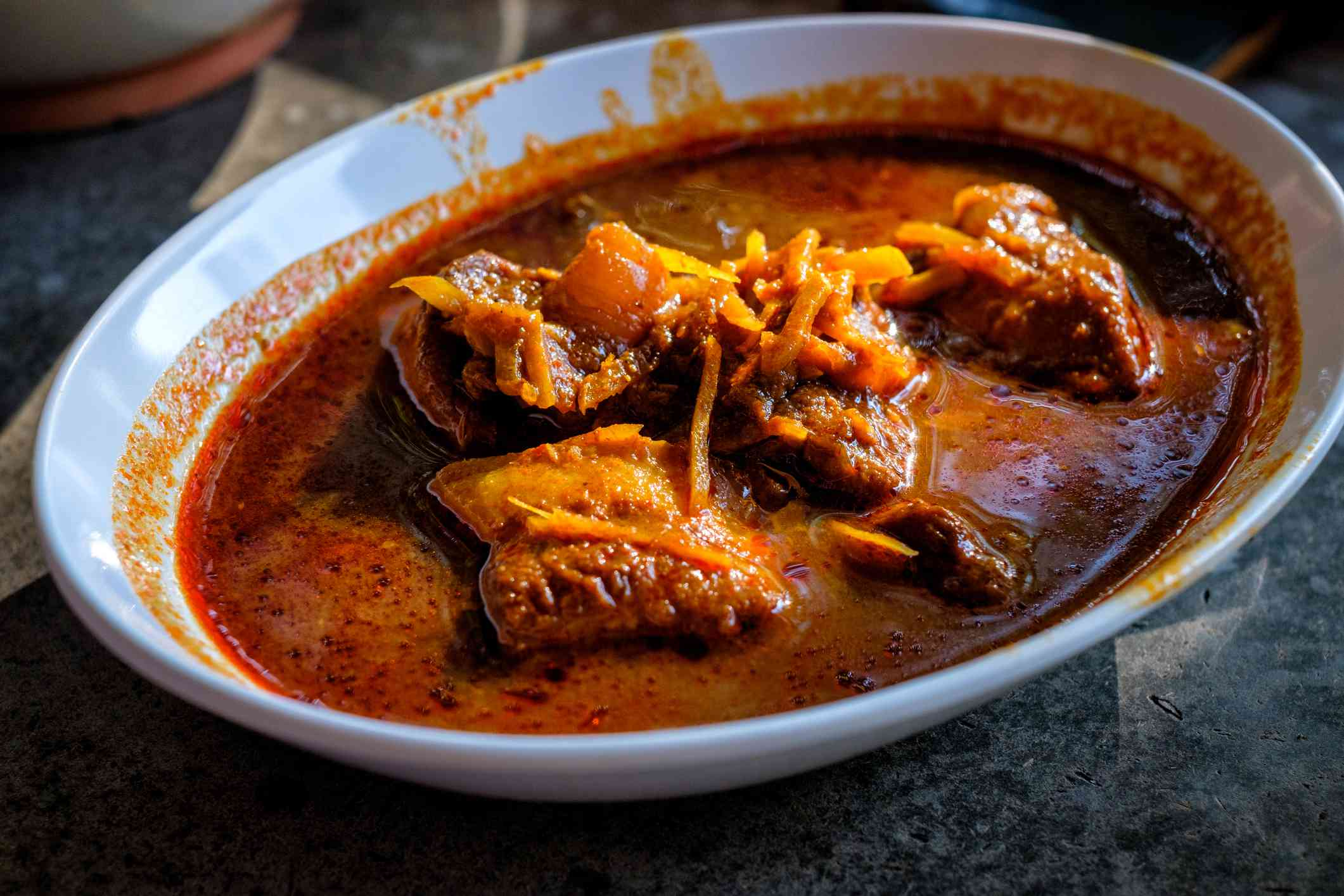 bowl of red curry with chunks of pork