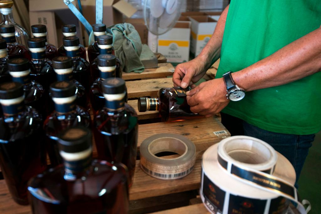 A worker manually labels bottles of old rum at the Bologne Rum Distillery in Basse-Terre