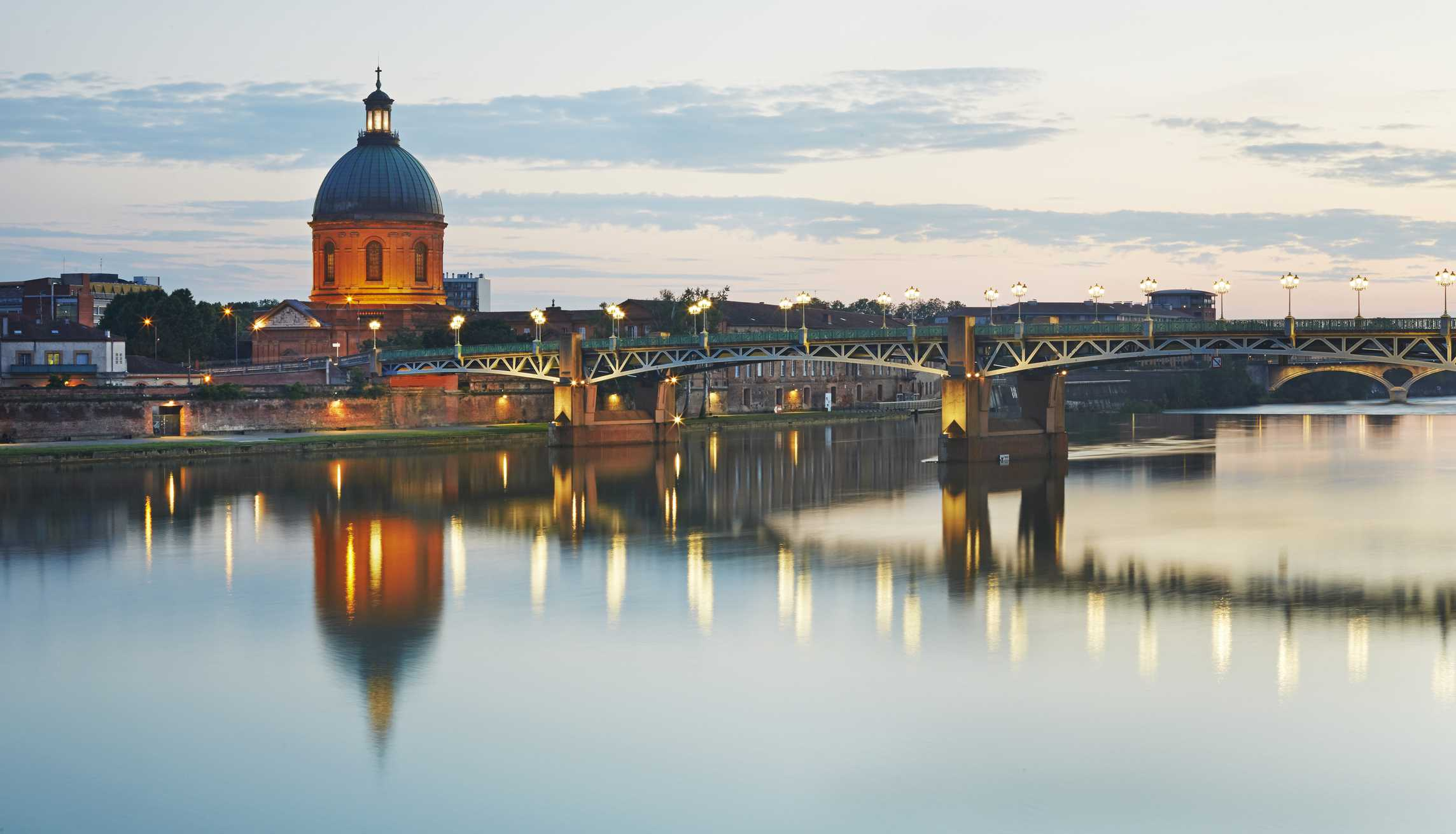 The dome of the 'Hopital de la Grave' with 'Pont Saint -Pierre' girder bridge illuminated at dusk over the Garonne River