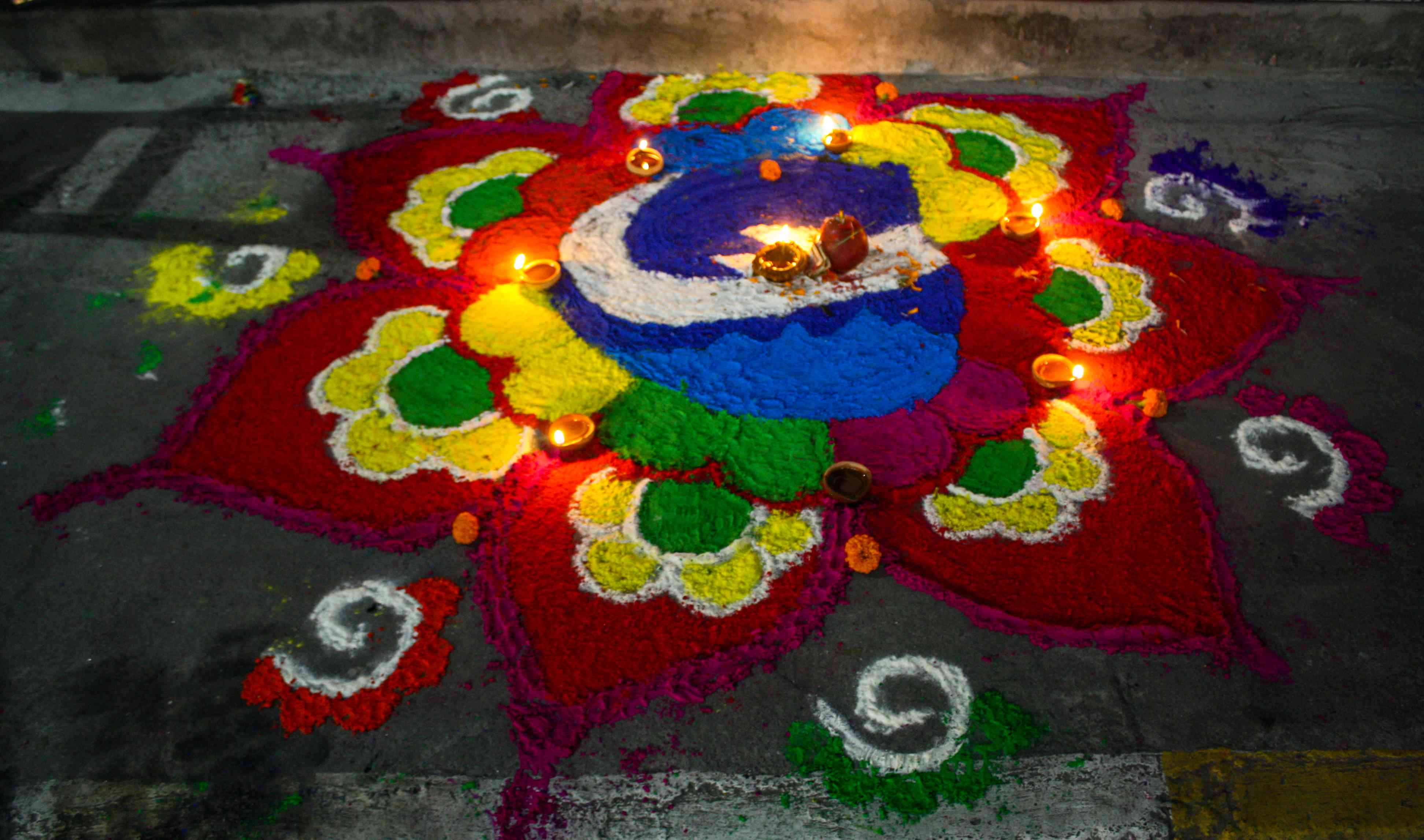 colorful powder design on the street surrounded by candles