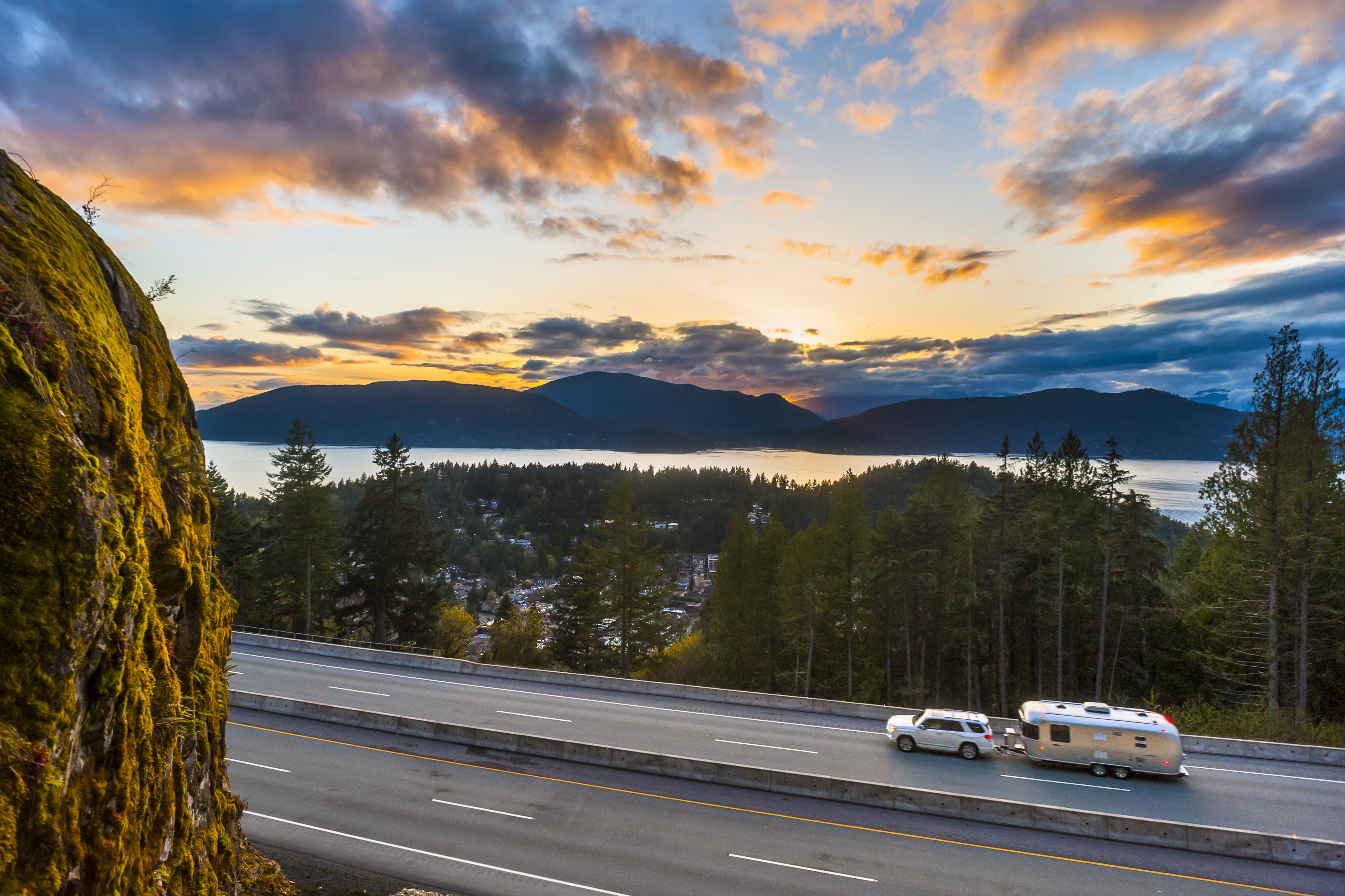 A car pulling a trailer on the sea to sky highway at sunset