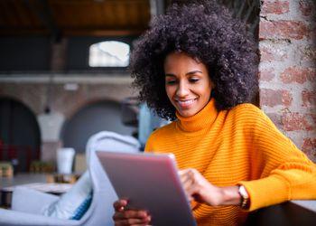 Smiling woman using digital tablet.