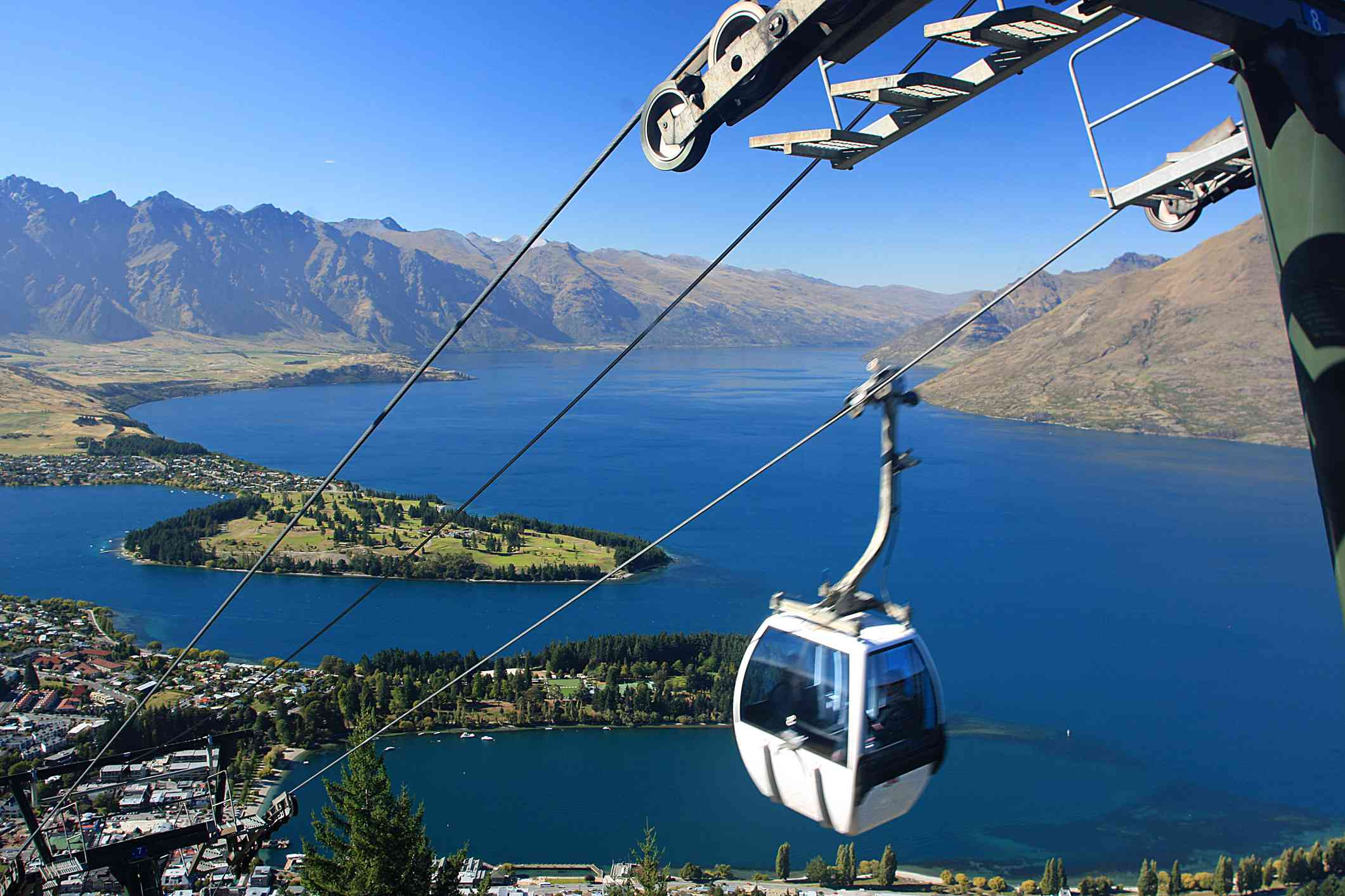 cable car above city and lake with mountains in background