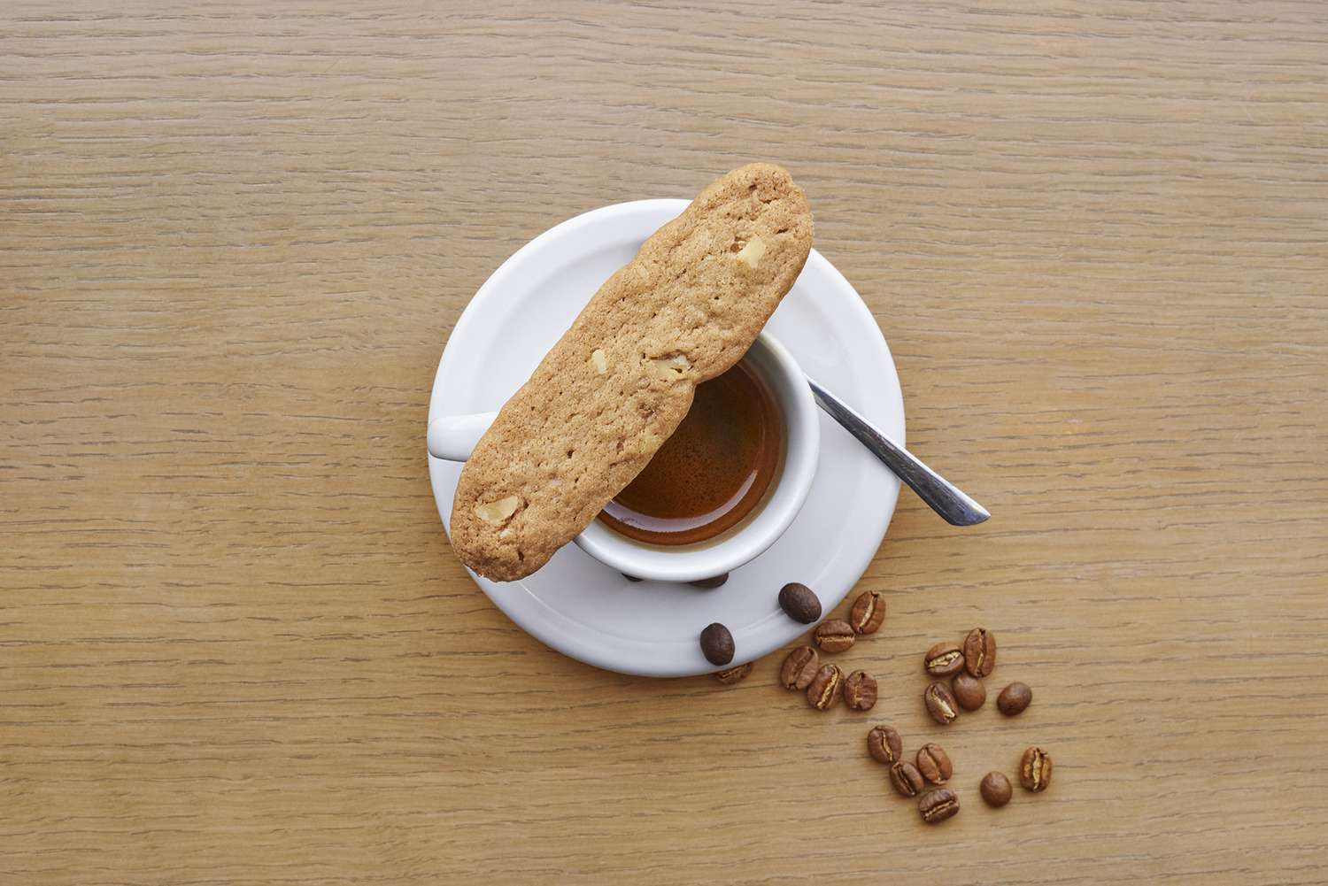 overhead shot of an oval-shaped cookie resting on an espresso shot with some coffee beans on the table