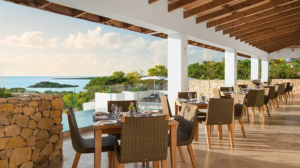 covered patio restaurant seating with a coastline in the distance