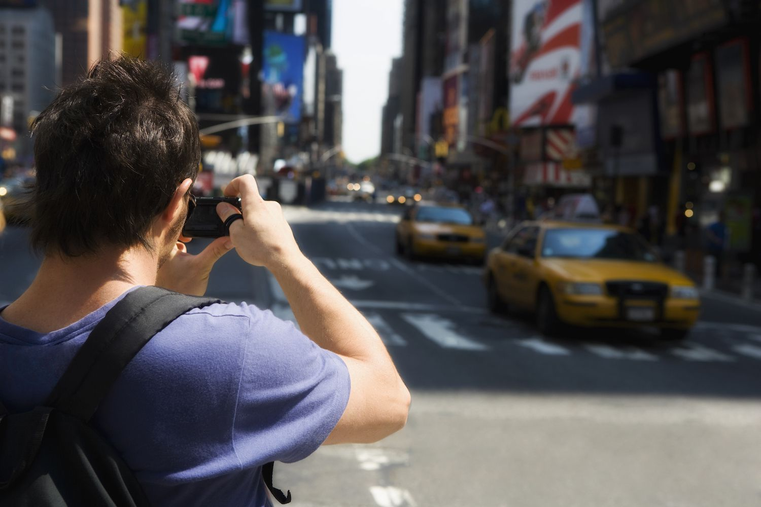 Rear view of a tourist photographing Times Square