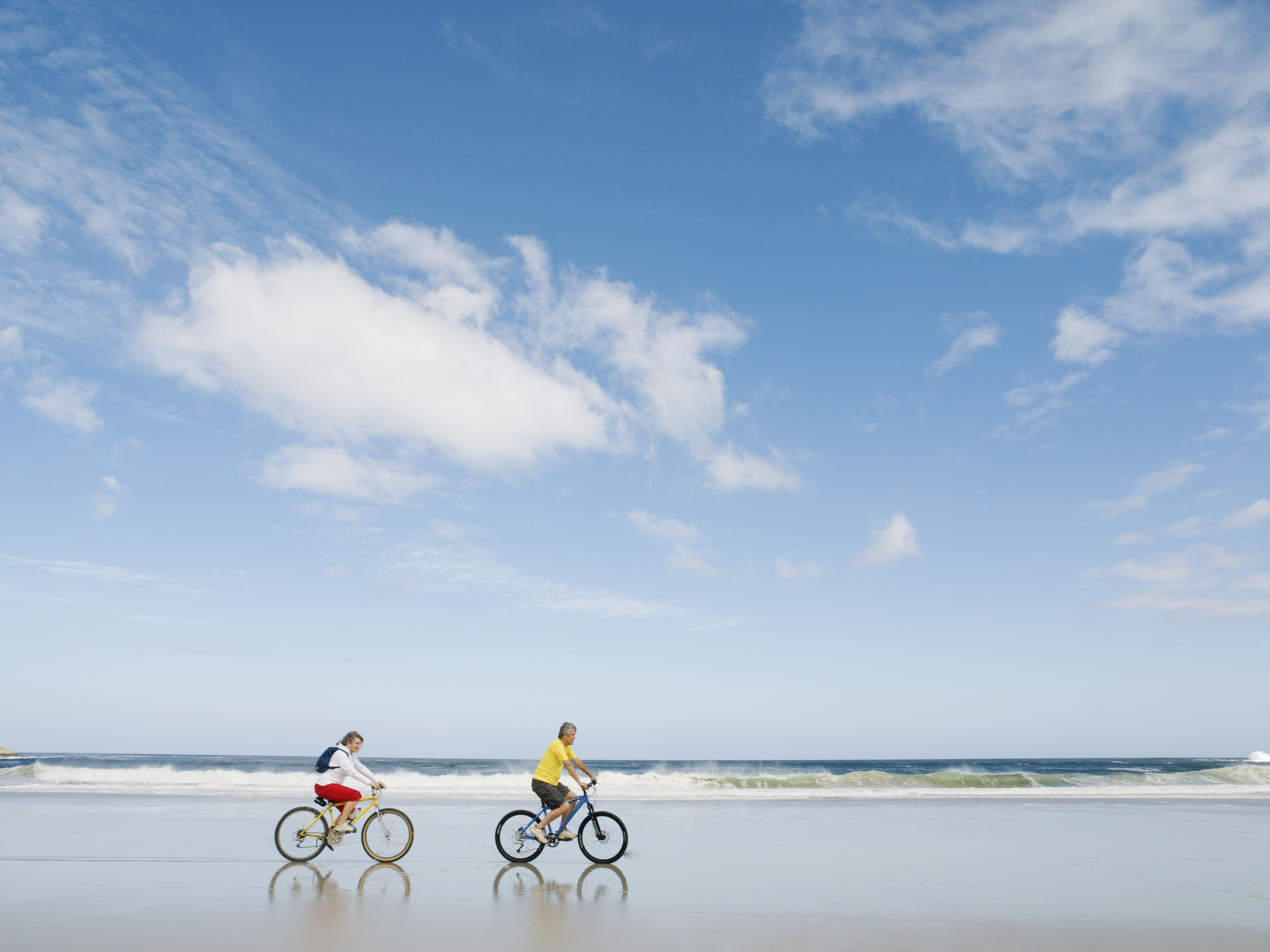 Mature couple riding bicycles on beach, side view