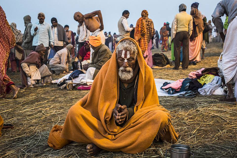 A 'sadhu' prays as he sits on the banks of Sangam