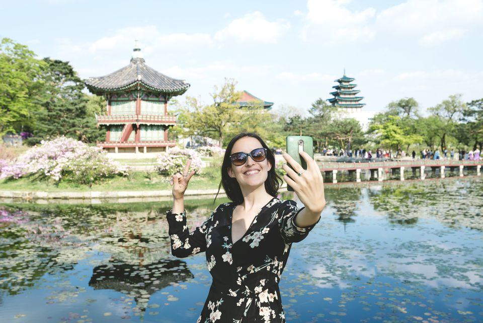 Woman taking a selfie with smartphone at Gyeongbokgung Palace in Seoul, South Korea
