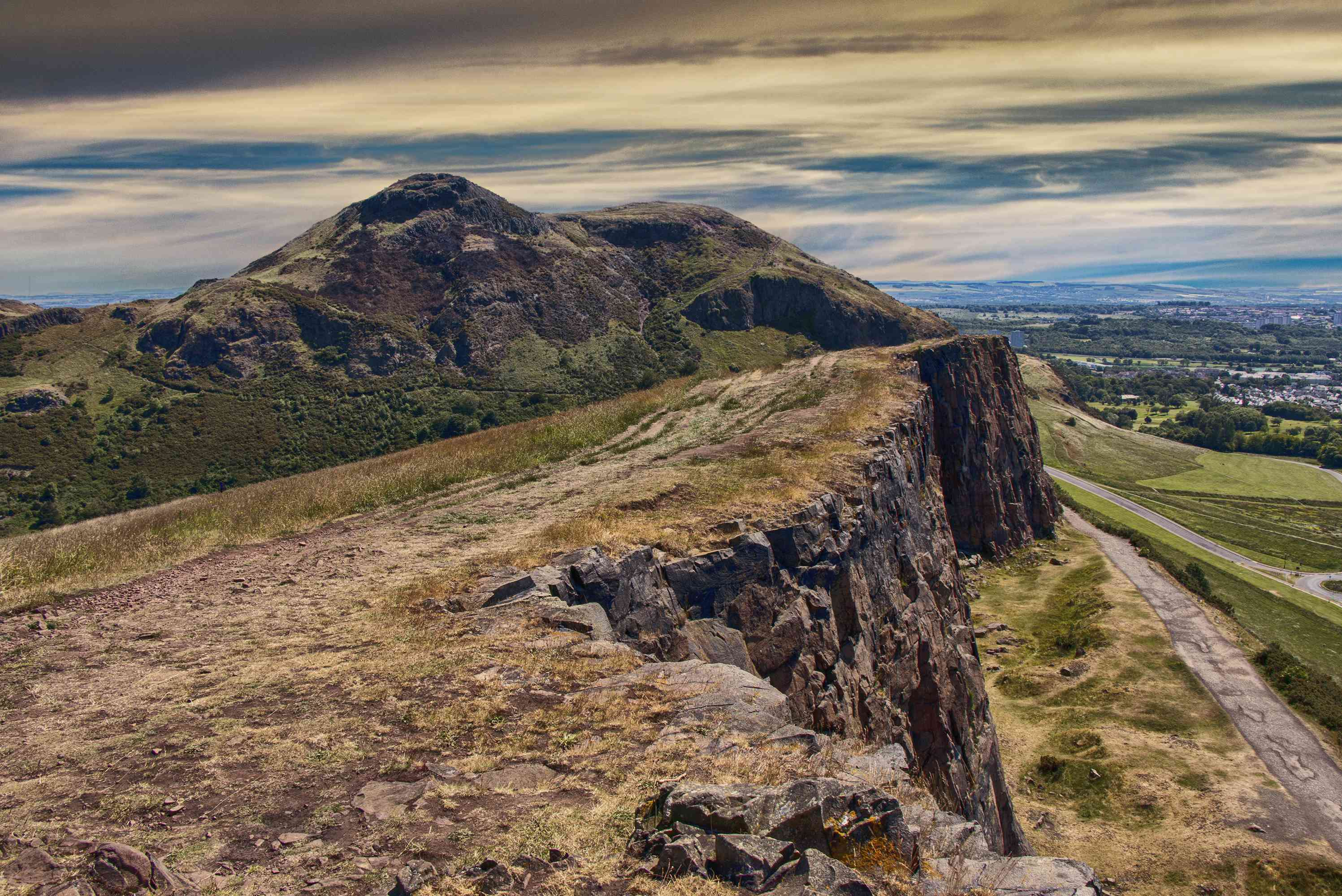 Arthur's Seat mountain in Scotland with path on the cliff and Edinburgh city in the background