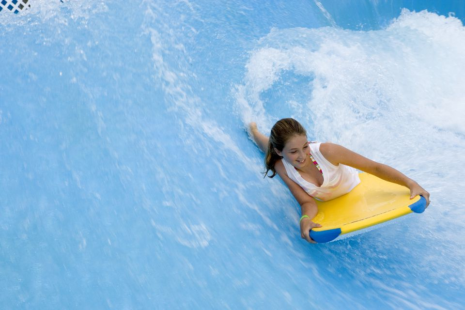 Girl (11-13) riding body board in water park