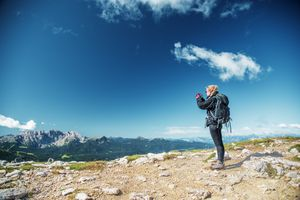 Female teenage hiker with rucksack in the Alps, taking images with camera
