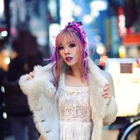 East asian woman with pink hair on a busy street wearing a white lacy dress and white faux-fur coat