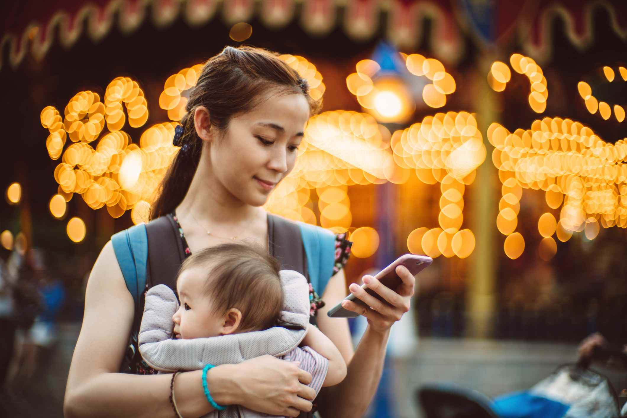 Young mom using her smartphone in theme park
