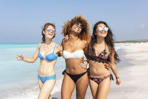 Happy girl friends walking on the beach