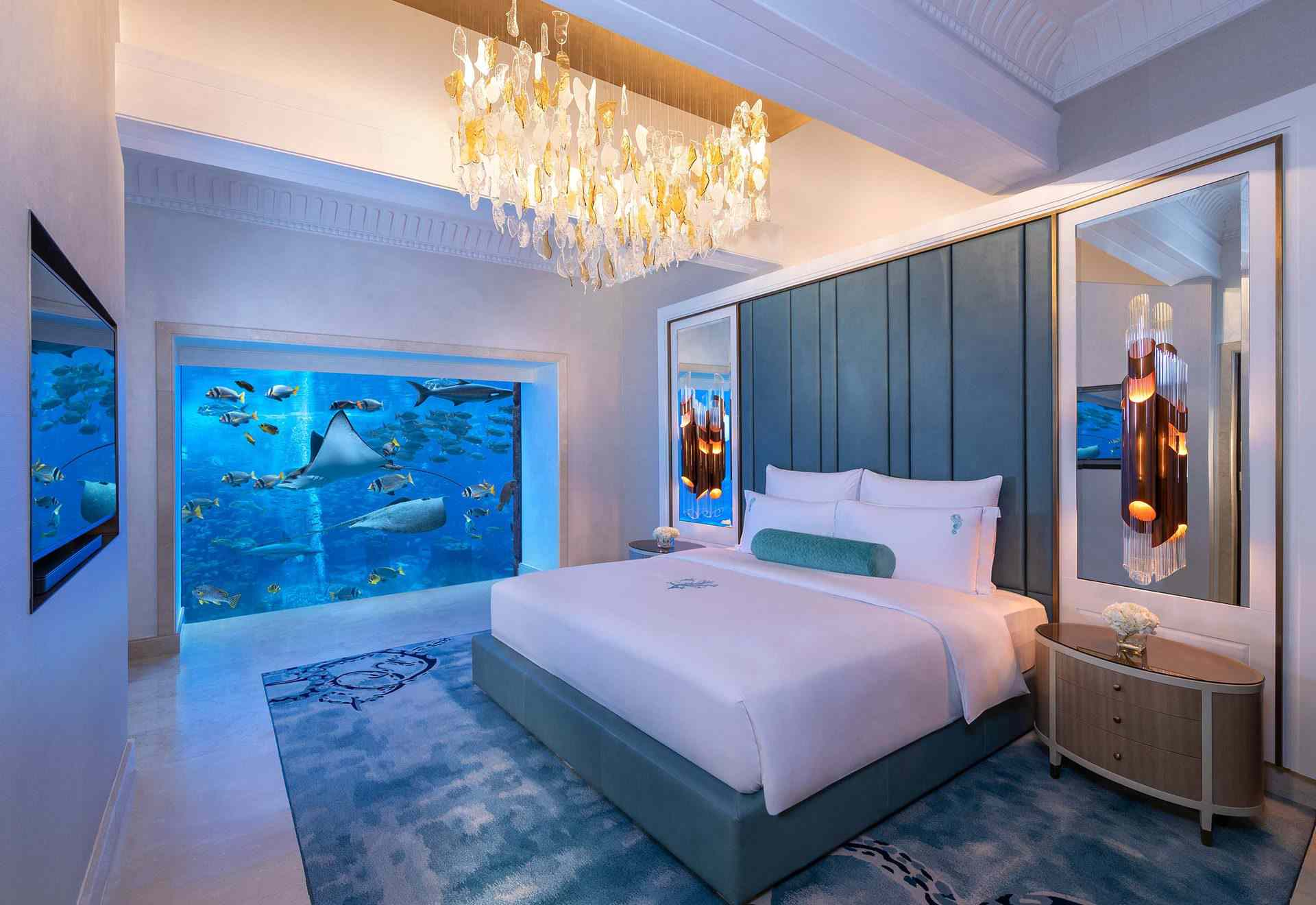 queen size bed in a hotel room with a blue and white theme. on the back wall there is a glass picture window showing sea life swimming by.