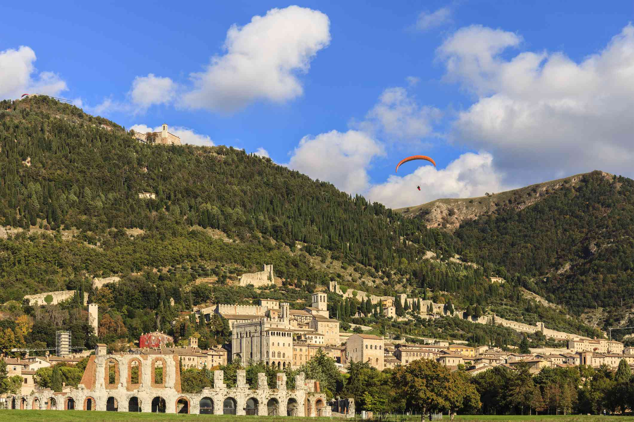 medieval town below a mountain and paraglider in the sky