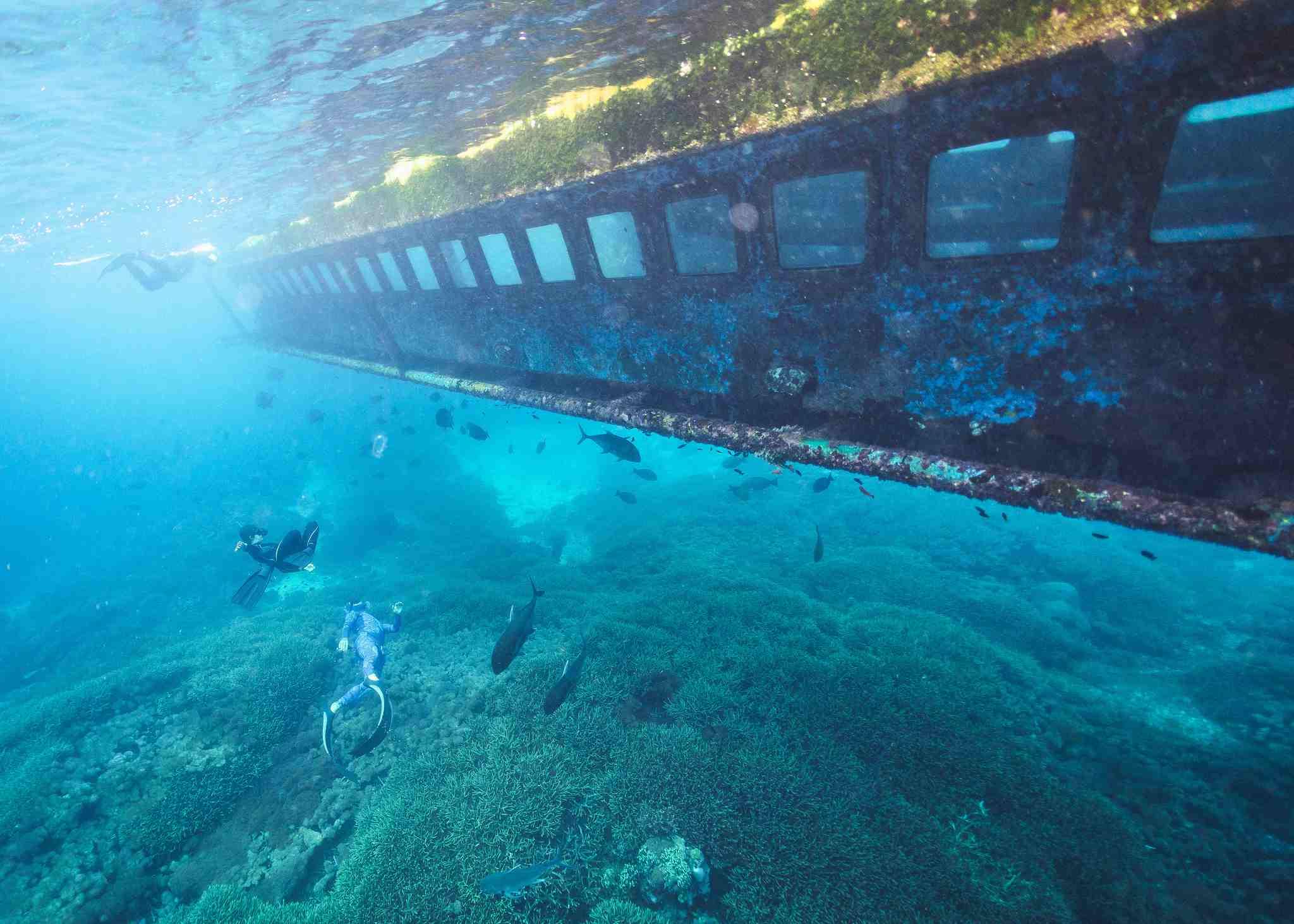 Sunken ship and free divers underwater, Nusa Penida, Bali, Indonesia