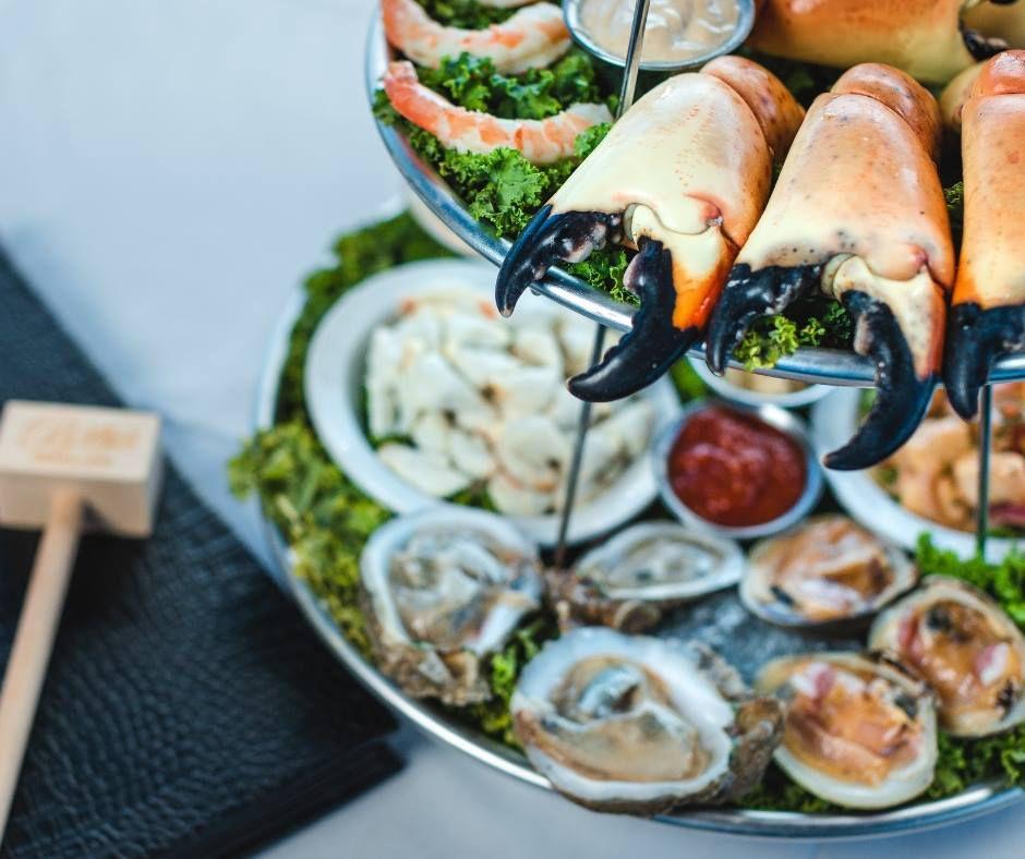 garras de cangrejo de piedra en una bandeja escalonada con ostras crudas y un mazo