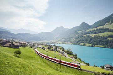 Lush Swiss landscape with commuter train and lake, Lungern, Obwalden, Switzerland