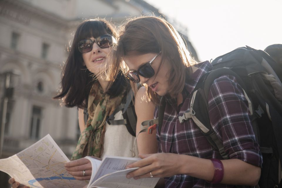 Two women backpackers sitting in sunlight reading map and guidebook