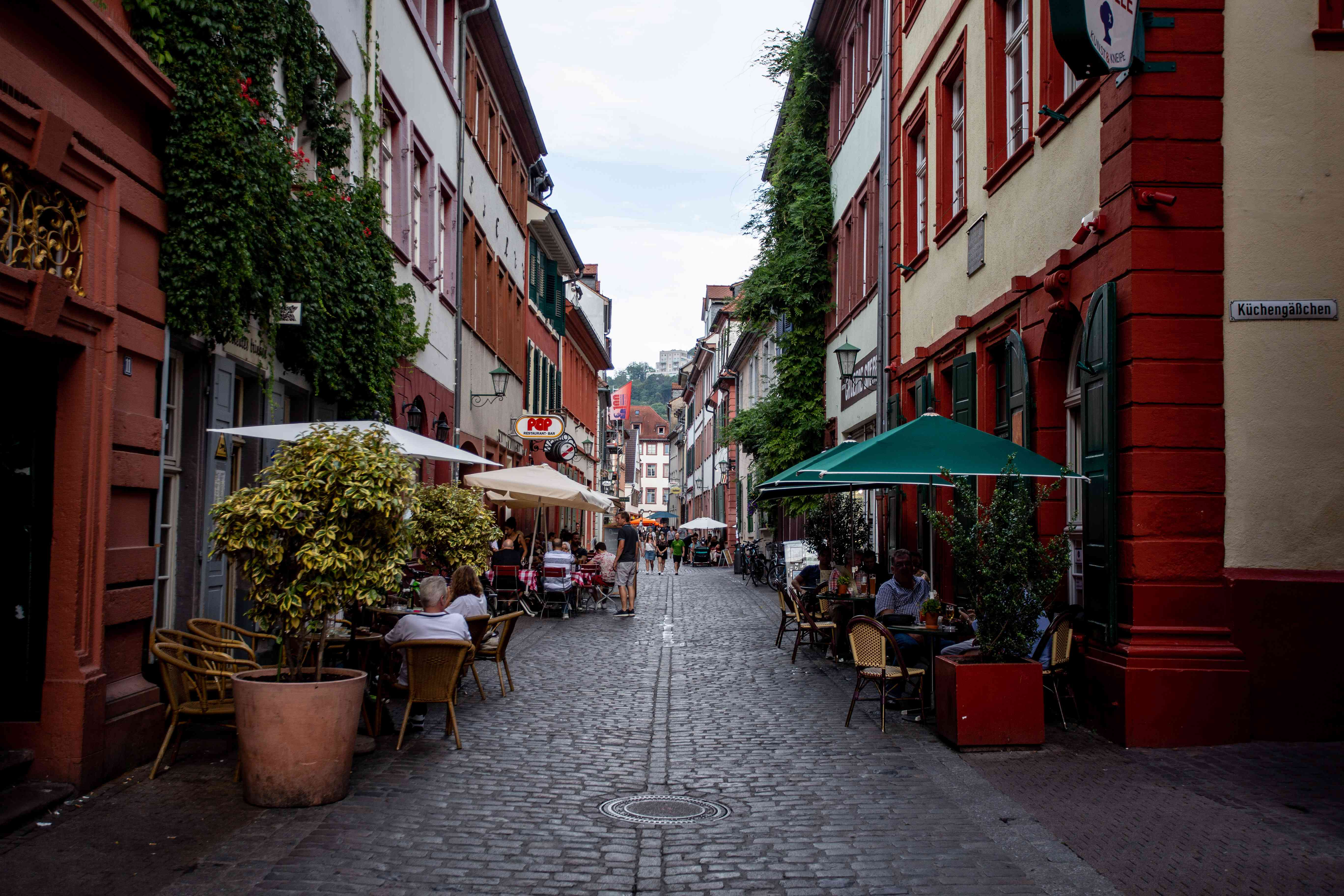 People sitting outside at cafes on a cobblestone alley of Untere Strasse