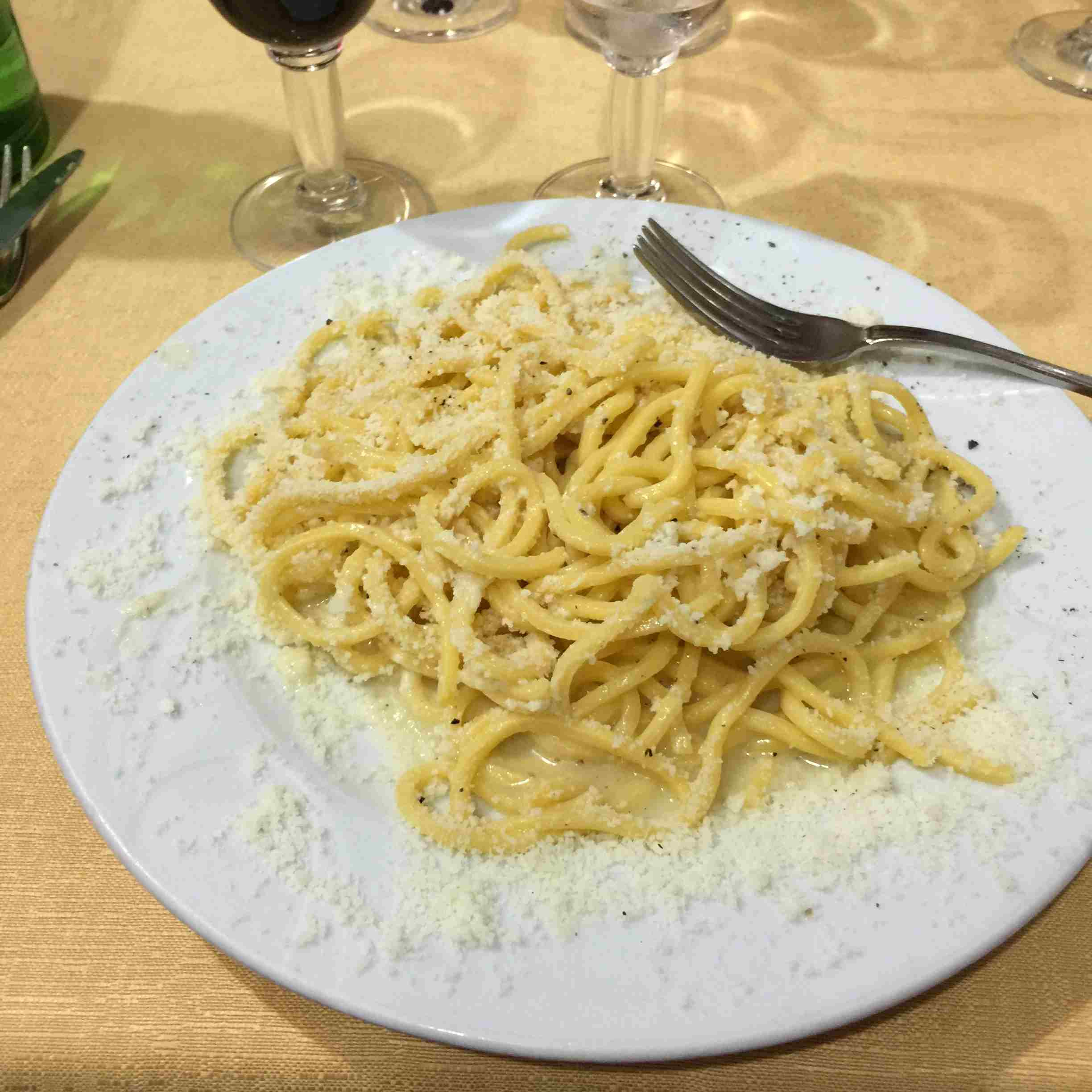 Close-Up Of Cacio E Pepe Served In Plate With Red Wine