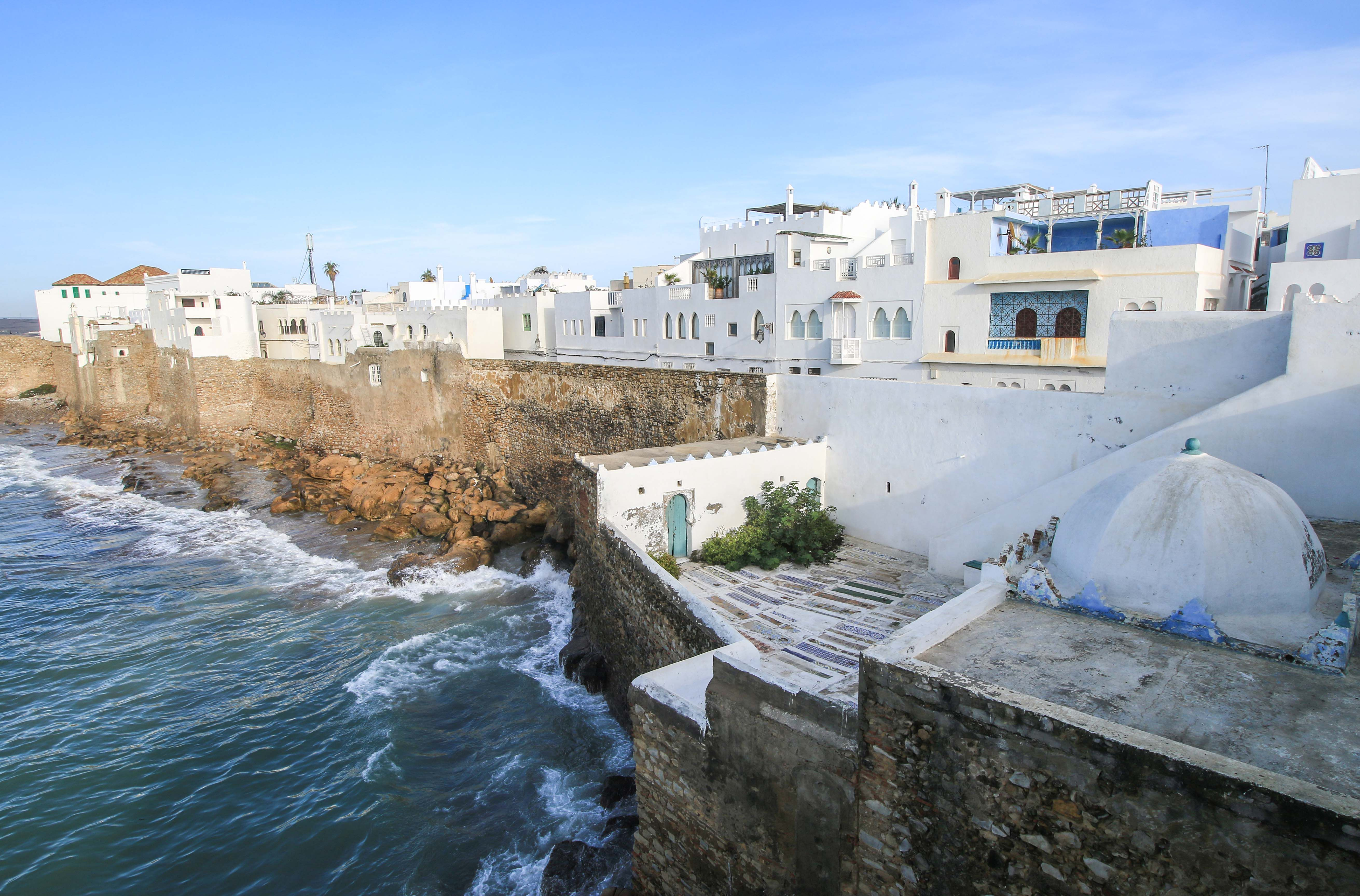A view of white buildings on a cliff above the sea