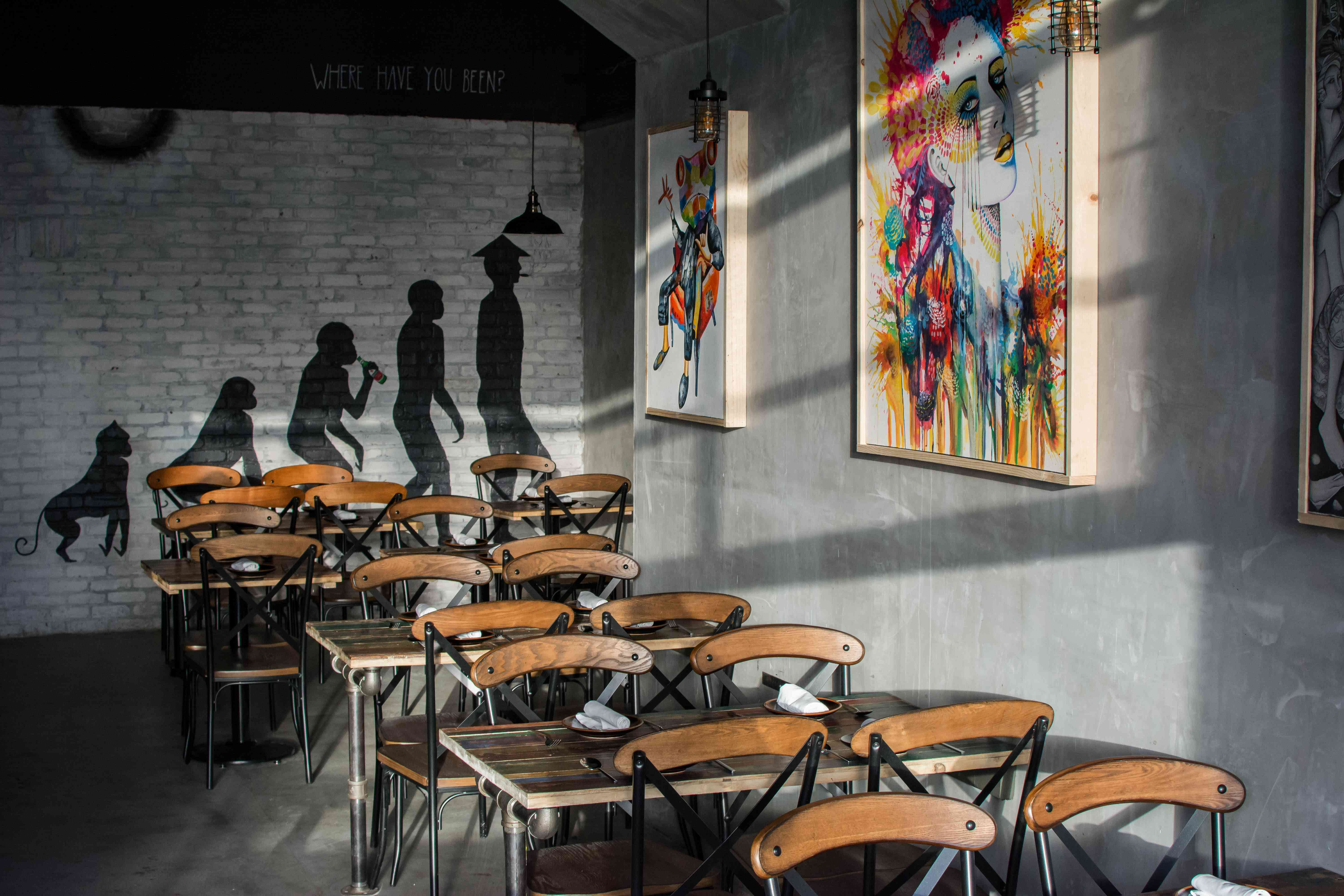 Chaires and tables in Dija Mara restaurant with colorful paintings on the gray walls