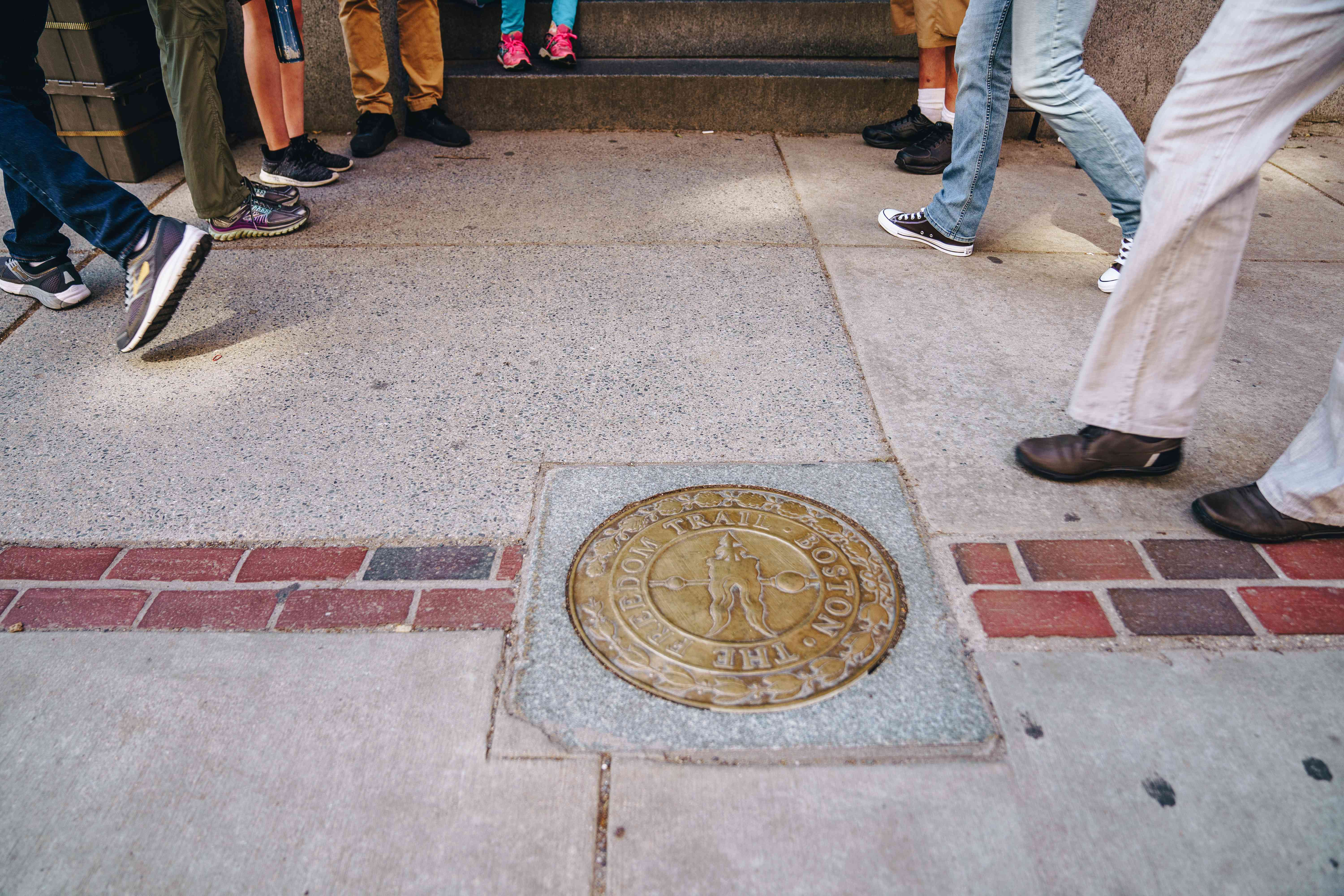 People walking by a Freedom Trail plaque