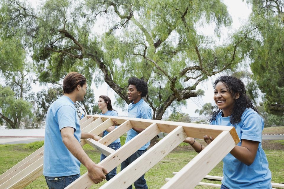 Happy volunteers lifting wooden frame together at park